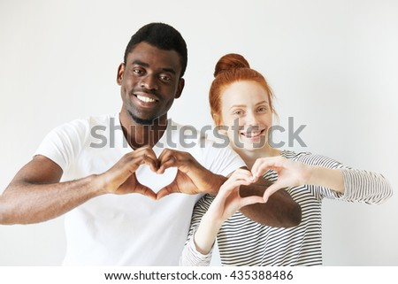 Happy youngsters showing love signs with their hands cupped in heart shape. Afro American man smiling with all his teeth and redhead woman with a bun on her head radiating positive emotions. - stock photo