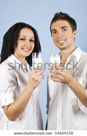 Happy youth couple standing together in front of image and holding glasses with milk on blue background - stock photo