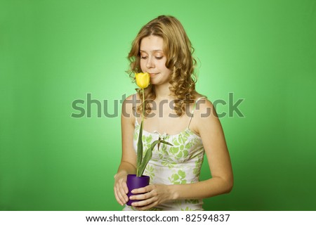 HappyClose up on a green background Happy young woman hugging a yellow tulip. Young Woman Hugging Flower
