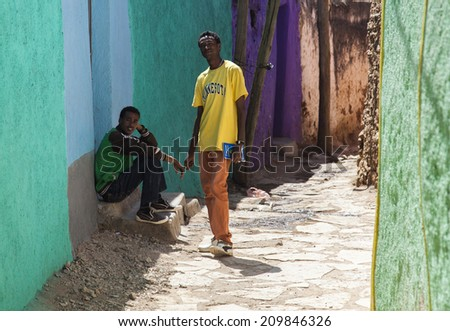 HARAR, ETHIOPIA - DECEMBER 24, 2013: Two unidentified young men posing in typical surroundings in ancient walled city of Jugol, that daily life is almost unchanged in more than four hundred years.