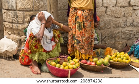 HARAR, ETHIOPIA - JULY 26,2014 - People sell vegetables on the streets of Jugul, the fortified historic walled city on UNESCO's World Heritage List, and considered as the fourth holy city of Islam. - stock photo