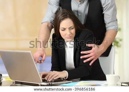 Harassment with a boss touching the arm to his secretary who is sitting in his workplace at office - stock photo