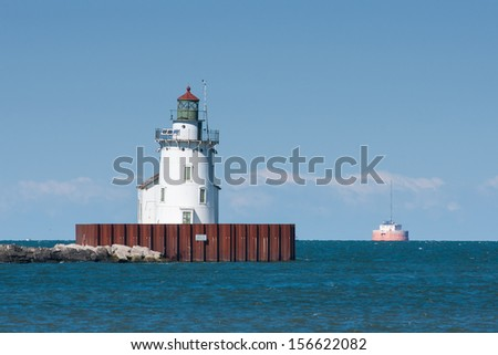 Harbor Beacon:  A navigation beacon, leaning from years of erosion and westerly winds, guards the entrance to the harbor at Cleveland, Ohio on Lake Erie - stock photo
