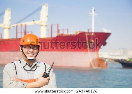 Harbor dock worker holding  radio and  ship background - stock photo