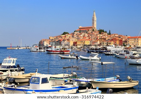 Harbor of an old Venetian town with traditional buildings and tall church above the sea, Rovinj, Croatia - stock photo