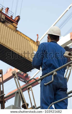 Harbor worker - watching the loading operation . Real situation photo. - stock photo