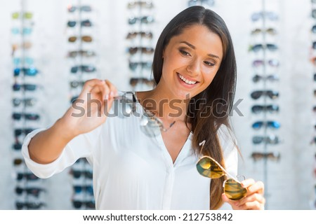 Hard choice. Beautiful young woman choosing sunglasses in store - stock photo
