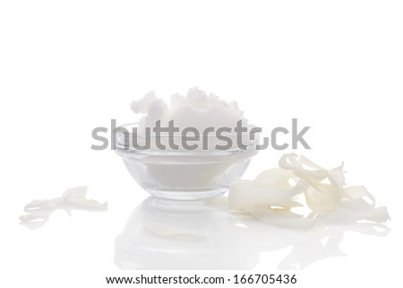 Hard coconut oil in glass bowl, dried coconut flakes on white background with reflection. Culinary healthy coconut oil background. Healthy cooking and bodycare still life. - stock photo