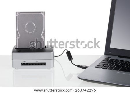 Hard disk drive with docking station connected to a laptop computer. For data storage. - stock photo
