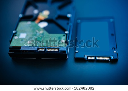 Hard disk next to ssd disk (solid state drive) blue technological background - tilt-shift lens used to accent the center of the hdd and to emphasize the attention their connections - stock photo
