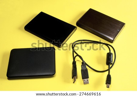 Hard disk portable on yellow background - stock photo