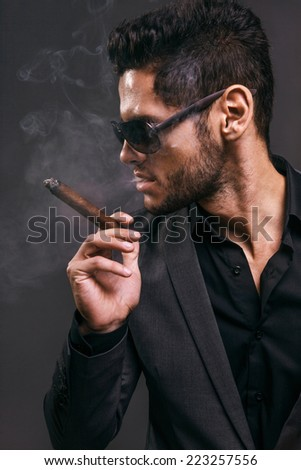 Hard gaze businessman while smoking a cuban cigar - stock photo