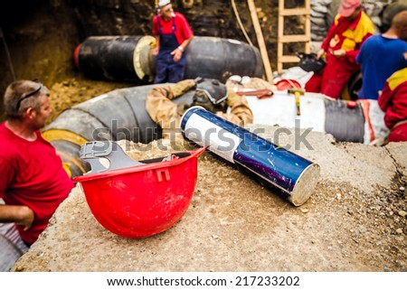 Hard hat and tin of electrodes for welding on the edge of trench, people blurred in background. - stock photo