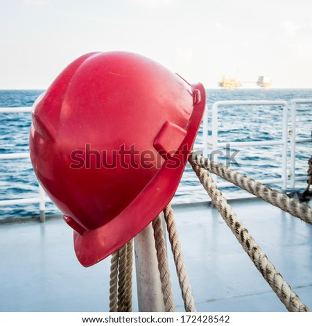 hard hat hanging on rope with oilfield background - stock photo