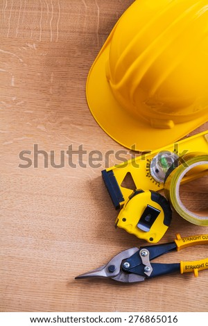 Hard hat nippers duct tape construction level and measuring tape on wood board