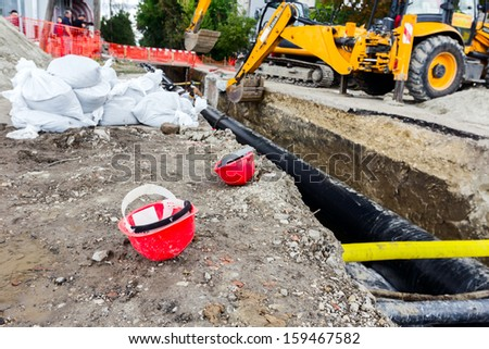 Hard hat on the construction site excavator on the background - stock photo