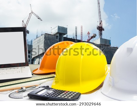 Hard hat over blurred construction site background - stock photo