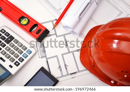 hard hat with blueprints, glove and caliper on table