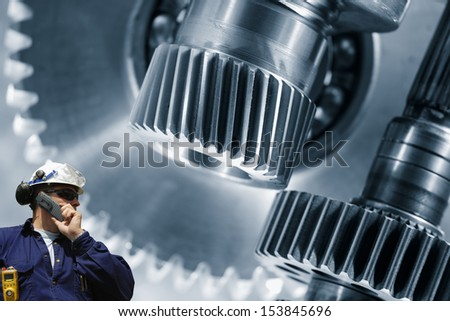 hard-hat worker with giant gears machinery in background, titanium and steel - stock photo