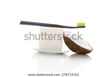 Hard organic coconut oil with toothbrush and coconut isolated on white background. Natural organic dental hygiene. - stock photo