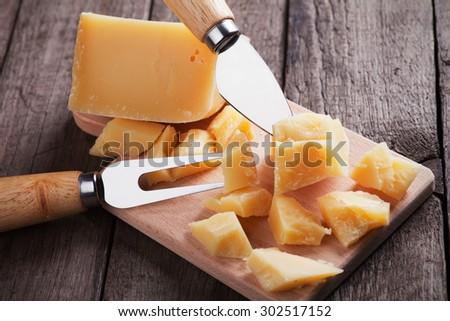 Hard, ripened parmesan or grana padano cheese on wooden board - stock photo