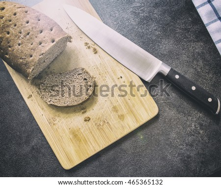hard stale bread and cut off a piece of it lie on a wooden cutting board, knife lying beside