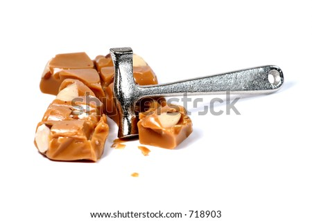 Hard toffee and small hammer on white background