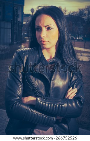 Hard toned image of brunette with crossed arms outdoors. - stock photo