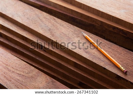 Hard wood lumber stacked with pencil on top. Wood working or interior carpentry. - stock photo