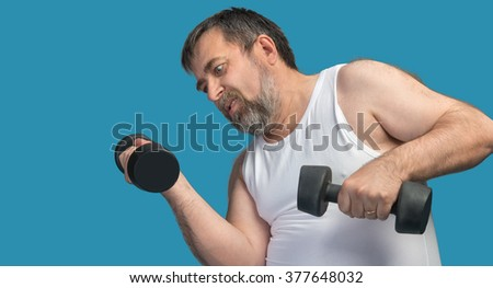 Hard work for a healthy lifestyle concept. The man does sports exercises isolated on blue with copyspace