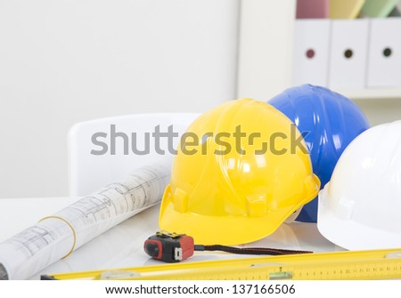 Hardhat  and measuring instruments on blueprint - stock photo