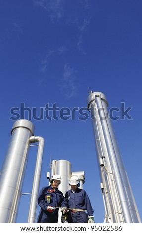 hardhat workers inside refinery, oil and gas pipes in background - stock photo