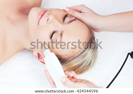 Hardware cosmetology. Closeup portrait of happy female face with closed eyes getting ultrasonic peeling in a beauty parlour.