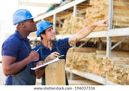 hardware store workers working in timber department - stock photo