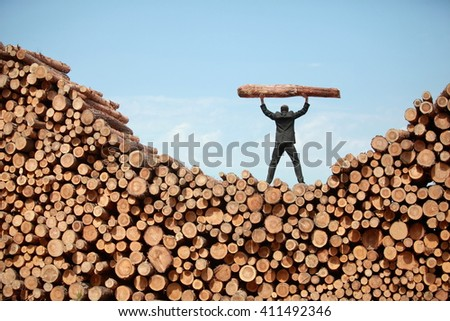 Hardworking Business Man on top of large pile of logs lifting heavy log - back view - stock photo