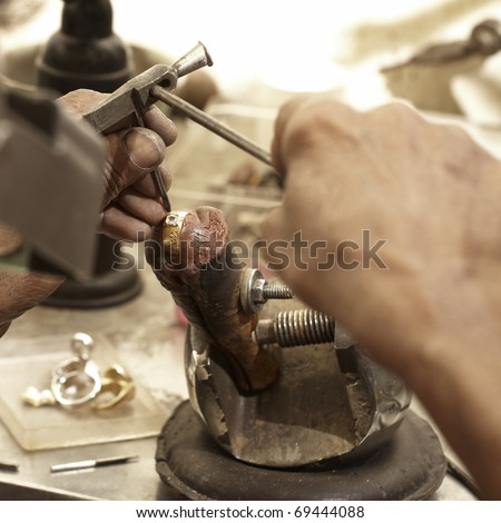 hardworking Goldsmith working on an unfinished 22 carat gold ring with his aged hands - stock photo