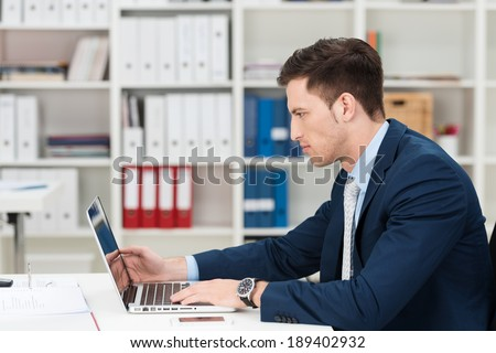 Hardworking young businessman at his desk frowning as he concentrates on information on the screen of his laptop computer, side view - stock photo