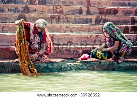 HARIDWAR - APRIL 11: Women washing their saris and clothing in holy Ganga river during Kumbha-mela festival. April 11, 2010 in Haridwar, India.