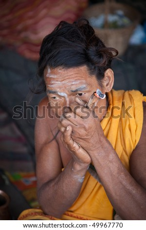 HARIDWAR, INDIA - MARCH 29: Sadhu, a Hindu holy man, smoking a chillum outside his tent during the Kumbh Mela festival March 29, 2010 in Haridwar, India.