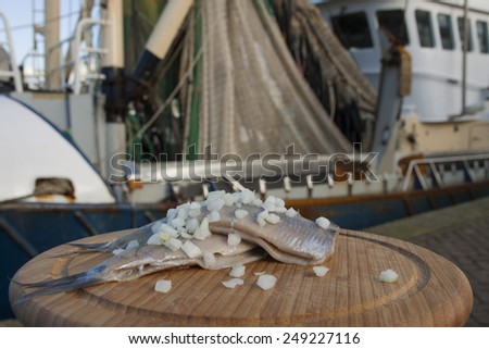 Haring with onion on a wooden plate with fishing boat - stock photo
