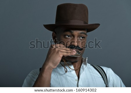 Harmonica playing retro afro america western cowboy man with mustache. Sitting in wooden chair. Wearing brown hat. Cool tough guy.