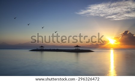 Harmony of life. The morning Sun rays warmth up the air of Sanur Beach and Mount Agung in Bali, Indonesia. - stock photo