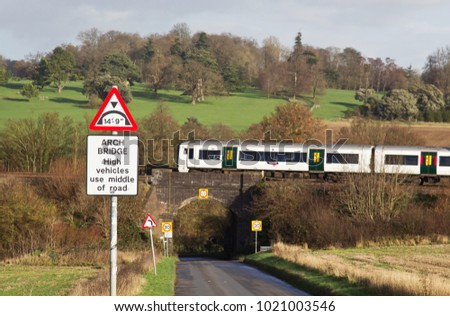 HARPENDEN, UK - DECEMBER 8: A new class 378 electric emu passes over a height restricted rural road bridge on route to Bedford with a commuter service on December 8, 2015 in Harpenden
