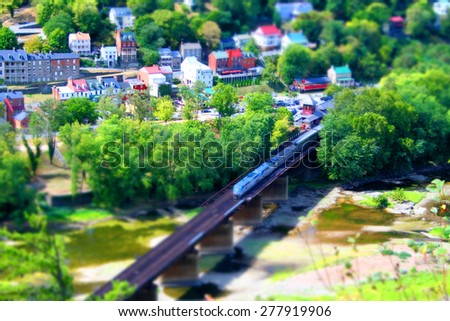 Harper's Ferry Miniature.  A view of Harper's Ferry, WV with a passenger train getting ready to cross the river. Historic Harper's Ferry district in the background. All made to look like a model. - stock photo