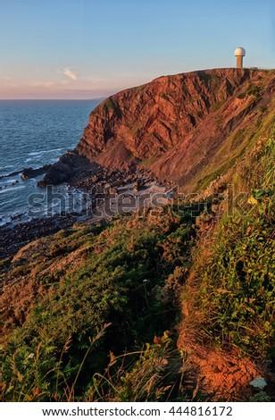 Hartland, Devon, England. Sea cliffs at sunset including the radar station. - stock photo