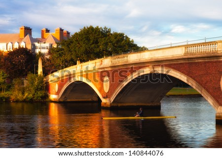Harvard University bridge over the Charles River in early morning golden light, with a lone sculler passing under the span - stock photo