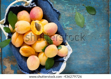Harvest fresh ripe peaches in a wicker basket on old wooden table, top view. - stock photo