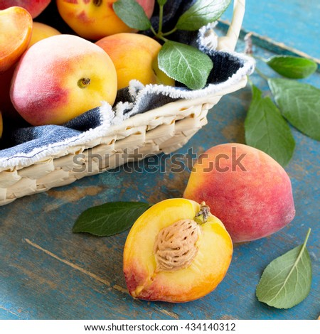 Harvest fresh ripe peaches in a wicker basket on the vintage wooden table, selective focus. - stock photo