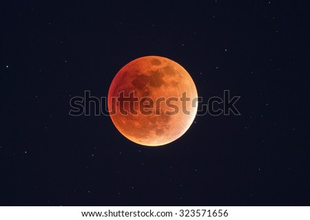 Harvest Moon Lunar Eclipse - Real Orange Super Blood Moon - Telescope view with night sky and stars in the background - stock photo