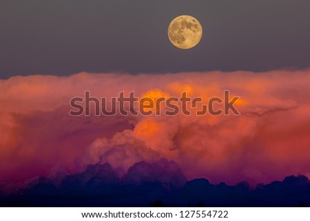 Harvest moon rising above storm clouds, southwestern Colorado - stock photo